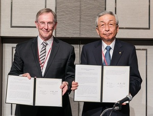 共同声明に署名する進藤委員長(右)